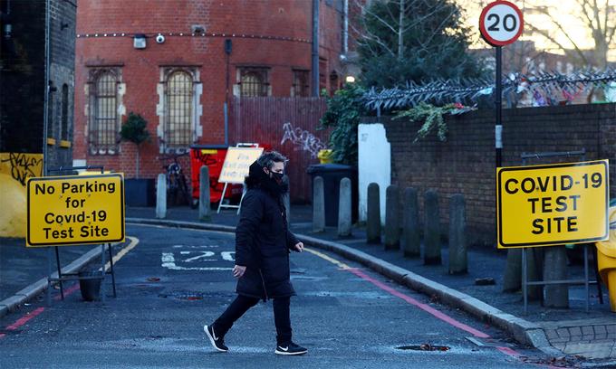 Một người đàn ông đi ngang qua lối vào khu lấy mẫu xét nghiệm Covid-19 tại London, Anh, ngày 21/1. Ảnh: Reuters.